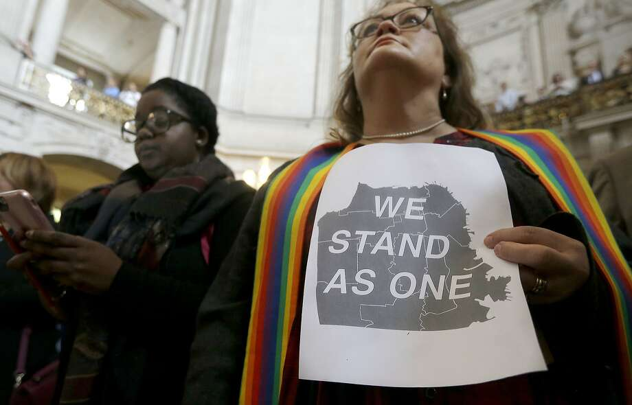The Rev. Annie Steinberg-Behrman, right, provisional pastor with Metropolitan Community Church, attends a November meeting at City Hall where officials and activists reaffirmed commitment to San Francisco as a sanctuary city in response to Donald Trump's support of deportations and other measures against immigrants. (AP Photo/Jeff Chiu) Photo: Jeff Chiu, Associated Press