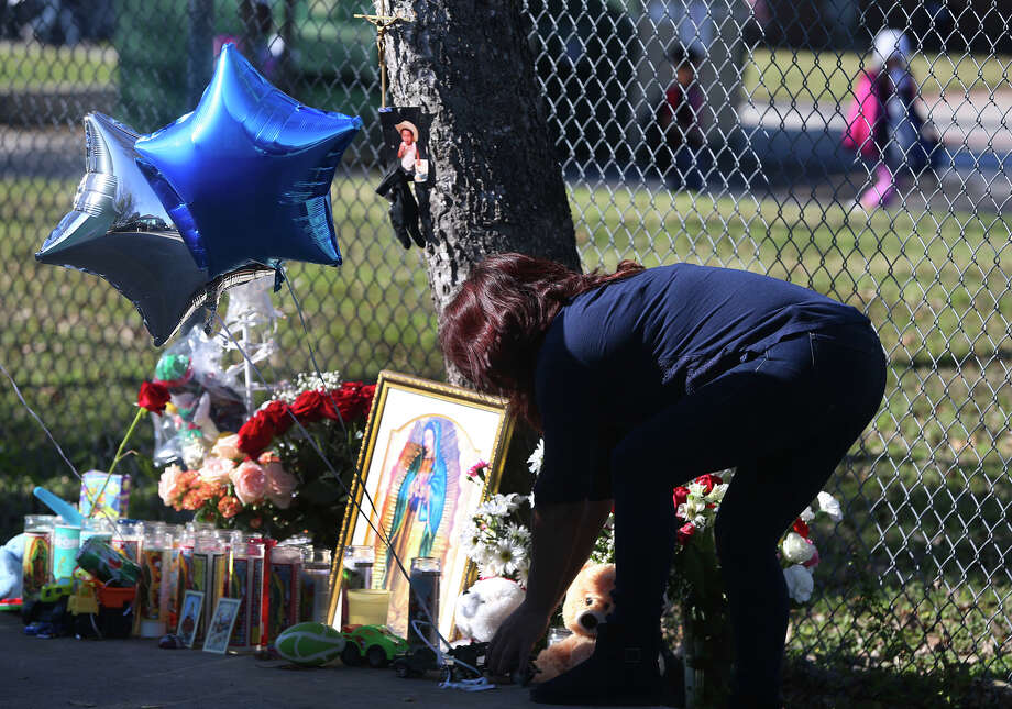 Sandra Mendez places balloons Tuesday December 13, 2016 at a small makeshift memorial by a fence that borders Olmos Elementary School a day after seven-year-old Brandon Castillo was hit by a car and killed on the 900 block of Allena. Mendez said she is a friend of the Castillo family. Photo: John Davenport, San Antonio Express-News / ©San Antonio Express-News/John Davenport