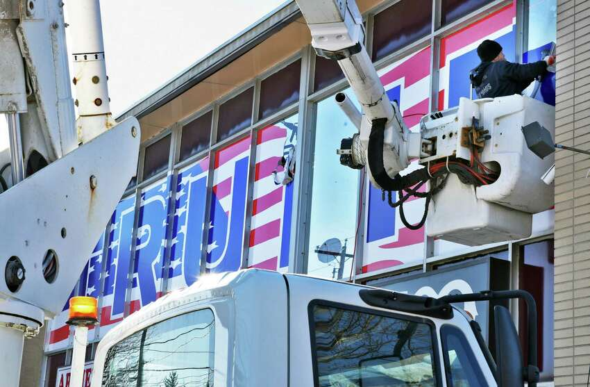 J.R. Cooke of Infamous Signs and Graphics removes a large TRUMP sign from American Shooters Supply on Central Avenue Tuesday Dec. 13, 2016 in Colonie, NY. Considering it a campaign sign, village officials have order the sign removed. (John Carl D'Annibale / Times Union)