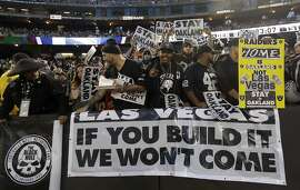FILE - In this Nov. 6, 2016, file photo, Oakland Raiders fans hold up signs about the team's possible move to Las Vegas during an NFL football game between the Raiders and the Denver Broncos in Oakland, Calif. City and county officials are expected to vote Tuesday, Dec. 13, 2016, on a deal for a new $1.3 billion stadium that supporters hope will keep the Oakland Raiders in town. (AP Photo/Marcio Jose Sanchez, File)