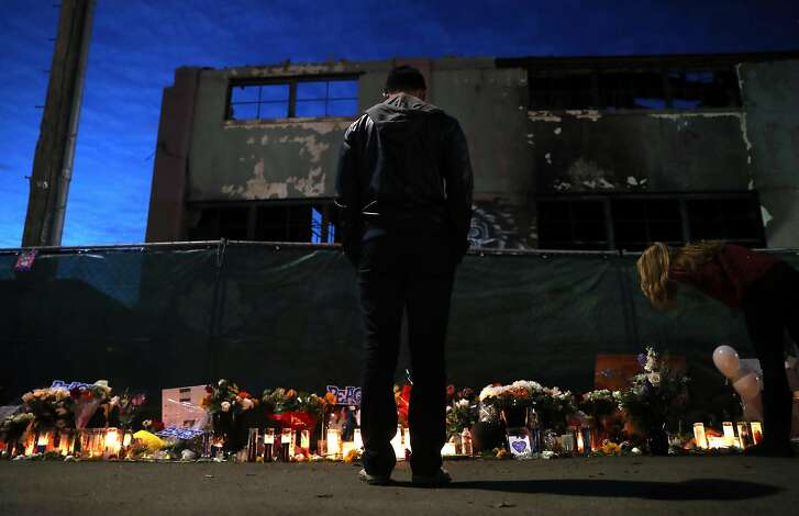 Edison Xu stands in front of the Ghost Ship warehouse near a memorial for fire victims on 31st Avenue in Oakland, Calif., on Monday, December 12, 2016.