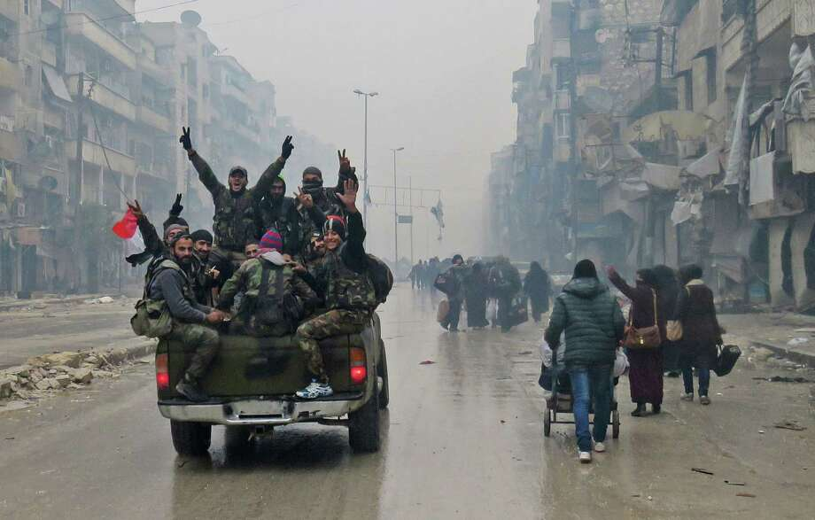 Syrian pro-regime fighters drive past residents fleeing violence, rebel forces and crumbling homes in the turbulent Bustan al-Qasr neighborhood of Aleppo as the Syrian government reestablishes control of the city. Photo: STRINGER, Stringer / AFP or licensors