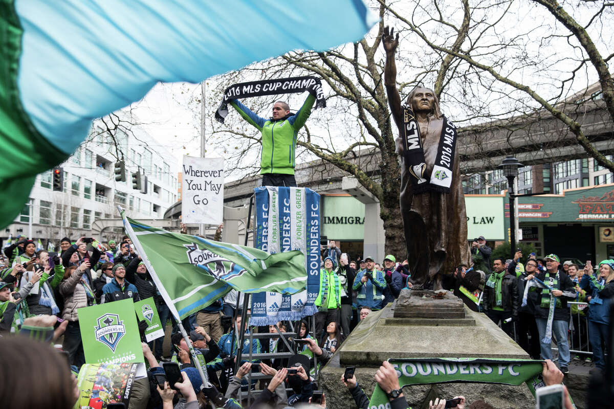 Sounders midfielder Osvaldo Alonso holds up an MLS Cup champions scarf next to the statue of Chief Seattle during a march celebrating their championship, on Tuesday, Dec. 13, 2016 in Seattle.