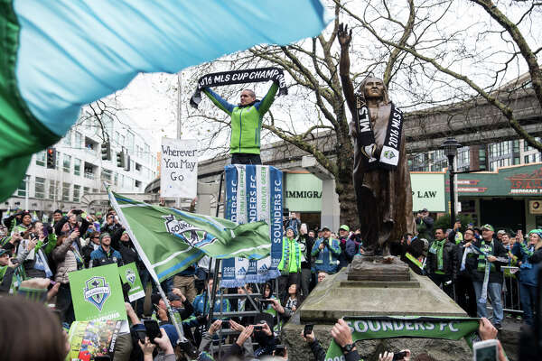 Sounders midfielder Osvaldo Alonso holds up an MLS cup champions scarf next to the statue of Chief Seattle during a march celebrating their recent championship, on Tuesday, Dec. 13, 2016.