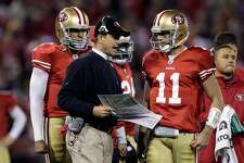 FILE - In this Dec. 19, 2011 file photo, San Francisco 49ers head coach Jim Harbaugh, center, talks with quarterback Alex Smith (11) during the second quarter of an NFL football game against the Pittsburgh Steelers in San Francisco. In the Bay Area, they're beginning to think about the possibility of Jim Harbaugh coaching former Indianapolis Colts quarterback Peyton Manning and believe it truly might happen. 49ers free agent quarterback Alex Smith traveled to Miami Sunday, March 18, 2012, to meet with the Dolphins. But if San Francisco doesn't sign Manning the 49ers will have some serious relationship-building to do with Smith. (AP Photo/Paul Sakuma, File)