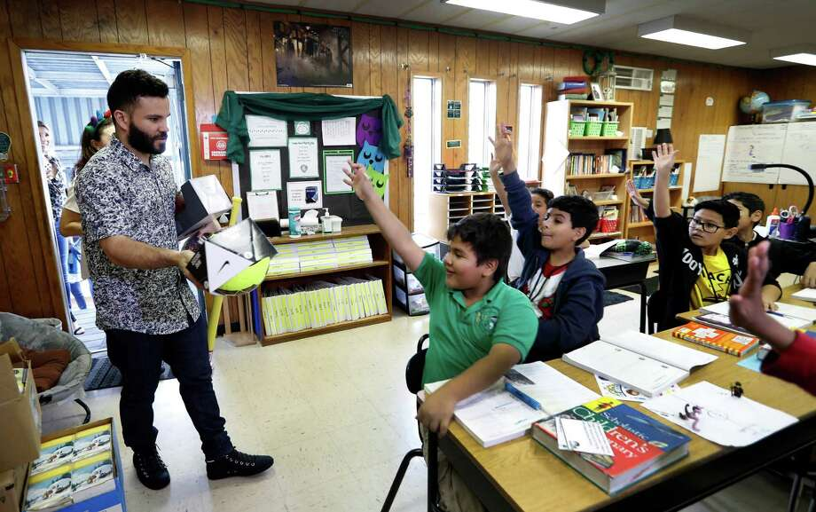 Astros second baseman Jose Altuve has an eager audience as he hands out Christmas gifts to students at Brookline Elementary School on Tuesday. Altuve partnered with Nan & Company Properties to deliver 1,000 books and 1,000 toys to 1,000 students at the school. Photo: Karen Warren, Staff Photographer / 2016 Houston Chronicle