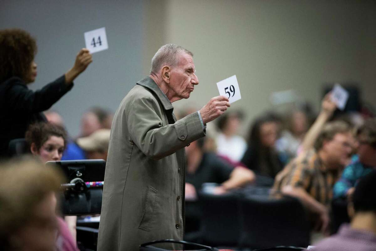 """Jim Sel, center, and others display their numbers to officials from the U.S. Department of Education and the Texas Education Agency in a bid to extend Monday's """"listening session"""" on special education in Texas."""