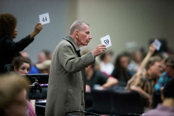 "Jim Sel, center, and others display their numbers to officials from the U.S. Department of Education and the Texas Education Agency in a bid to extend Monday's ""listening session"" on special education in Texas."