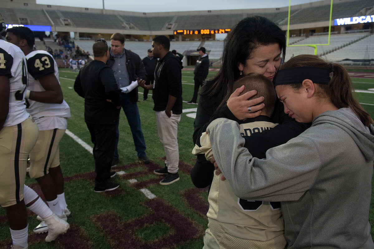 Lisa McDowell, bottom center, the wife of Richmond Foster Head Football Coach Shaun McDowell, consoles their son Bubba, 9, left, a 3rd grader at Frost Elem., and their daughter Ella, 10, a 5th grader at Frost Elem., while her husband, back left, answers questions from the media after the Falcon's 31-24 loss to Temple in their Class 5A Division I state semifinal matchup at Bobcat Stadium on the campus of Texas State University in San Marcos on Saturday, Dec. 10, 2016. (Photo by Jerry Baker/Freelance)