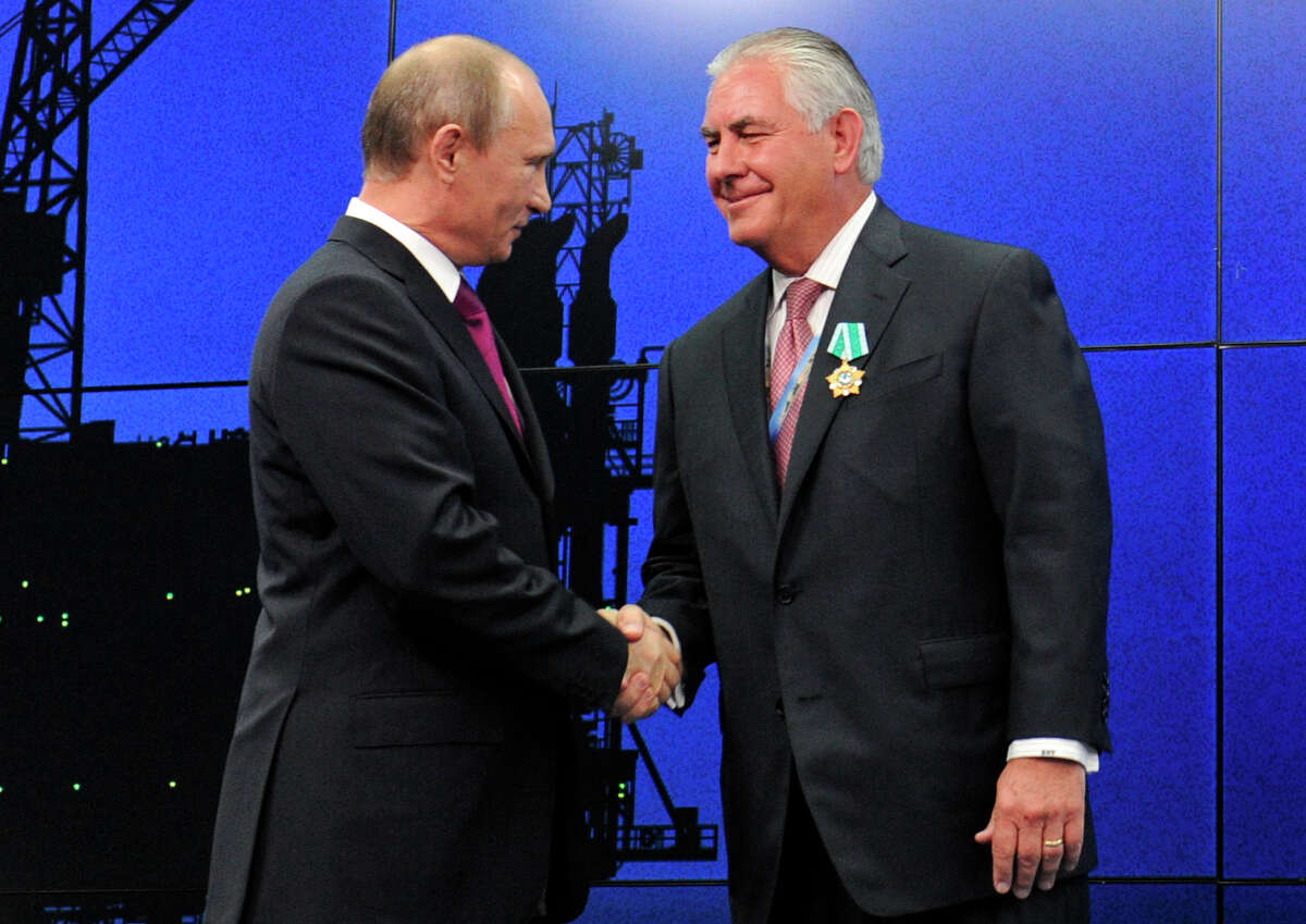 In this photo taken Thursday, June 21, 2012, Russian President Vladimir Putin presents ExxonMobil CEO Rex Tillerson with a Russian medal at an award ceremony of heads and employees of energy companies at the St. Petersburg economic forum in St. Petersburg, Russia. An aide to President Vladimir Putin praised United States President-elect Donald Trump?'s choice of Rex Tillerson to lead the State Department and says that the businessman is well regarded by many Russian officials. (Mikhail Klimentyev/Sputnik, Kremlin Pool Photo via AP)
