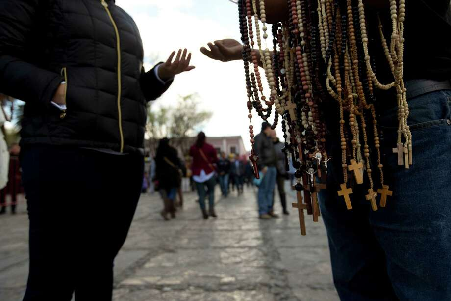 FILE - In this Feb. 14, 2016 file photo, a woman buys a rosary from a street vendor, in San Cristobal de las Casas, Mexico. On Monday, Pope Francis will travel to the southern indigenous state of Chiapas, Mexico's poorest and least Catholic region. A new study released by the National Statistics Institute Tuesday, Dec. 13, 2016, finds that about 58 percent of jobs in Mexico are in the informal sector, which includes categories such as unregistered vendors, artisans and domestic workers. (AP Photo/Moises Castillo, File) Photo: Moises Castillo, STF / Copyright 2016 The Associated Press. All rights reserved.