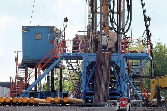 A crew works on a gas drilling rig at a well site for shale-based natural gas in Zelienople, Pa. An EPA report on possible harm from hydraulic fracturing is inconclusive.