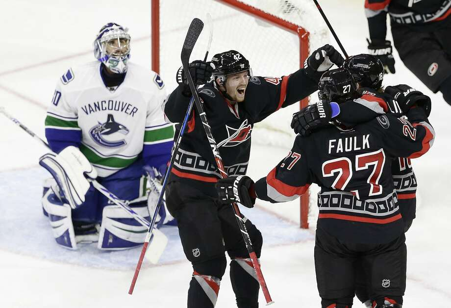 Vancouver goalie Ryan Miller (left) looks on as Carolina's Joakim Nordstrom and Elias Lindholm congratulate Justin Faulk (27) after Faulk's go-ahead goal during the third period. Photo: Gerry Broome, Associated Press