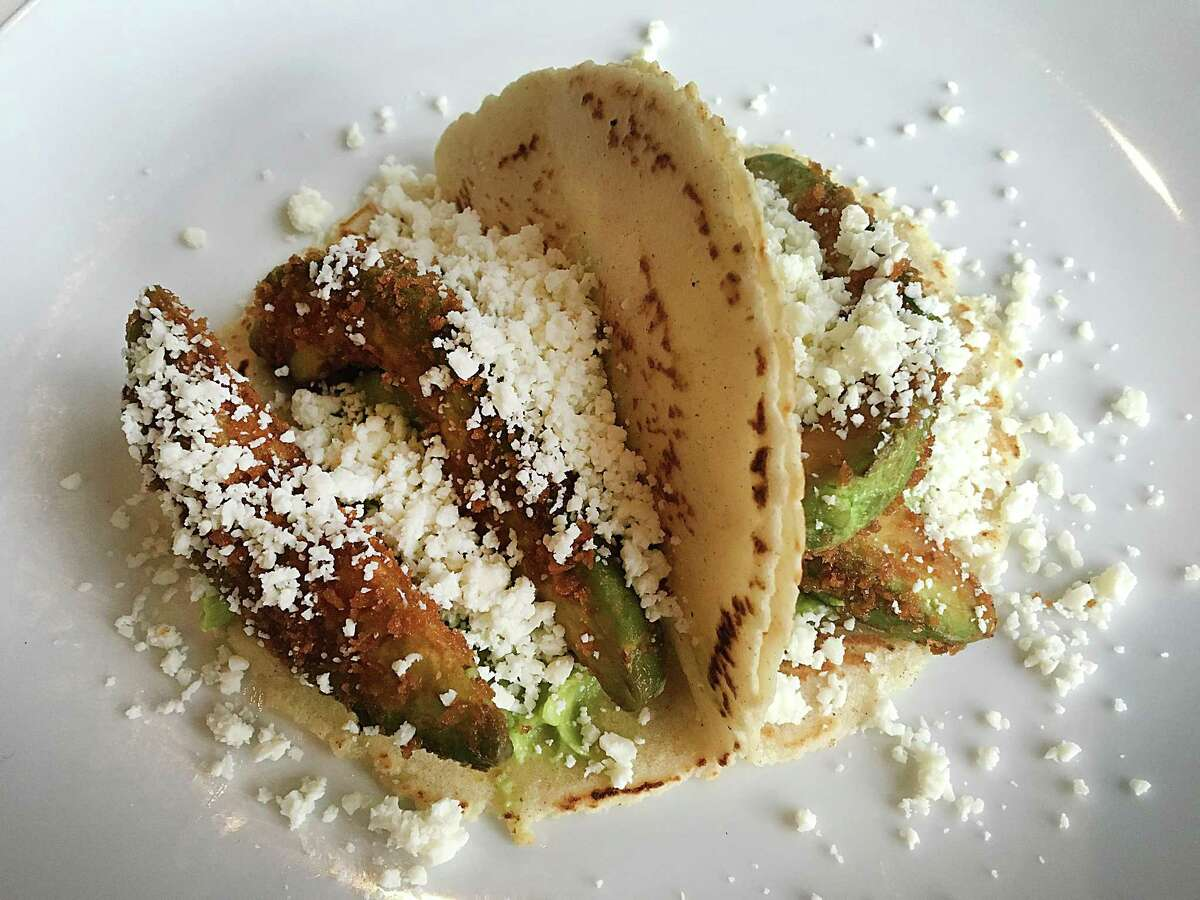 Fried avocado tacos with cotija cheese, guacamole and cilantro on handmade corn tortillas from Chisme.