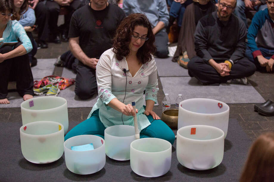 Dana Shamas of Bayou Bliss Yoga leads a session o crystal bowl meditation. The bowls are made of pure quartz and create a sound that helps people focus and relax. / Runaway Productions LLC