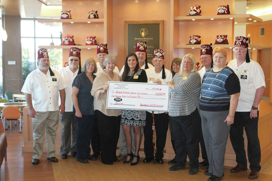 The Ladies of Moose present a check to St. Louis Shriners Hospital with the Troy/Edwardsville Shrine Club. In the past three years the Ladies of the Edwardsville Moose has raised over $4,000 for the St. Louis Shriner Hospital for Children. In front from left are:  Judy Graves, Cathy Gunderson Straub, Sarah Koehler-Dahlgren, Denise M. Matthews, Lisa Jackson Weber. In back from left are:  Harry Stewart, Gary Bean, Rodney Bruner, George Bruner, Carl Hall, Janet Cline (Shrinier's Hospital Administrator) Brian Brown and Don Sonneberg.