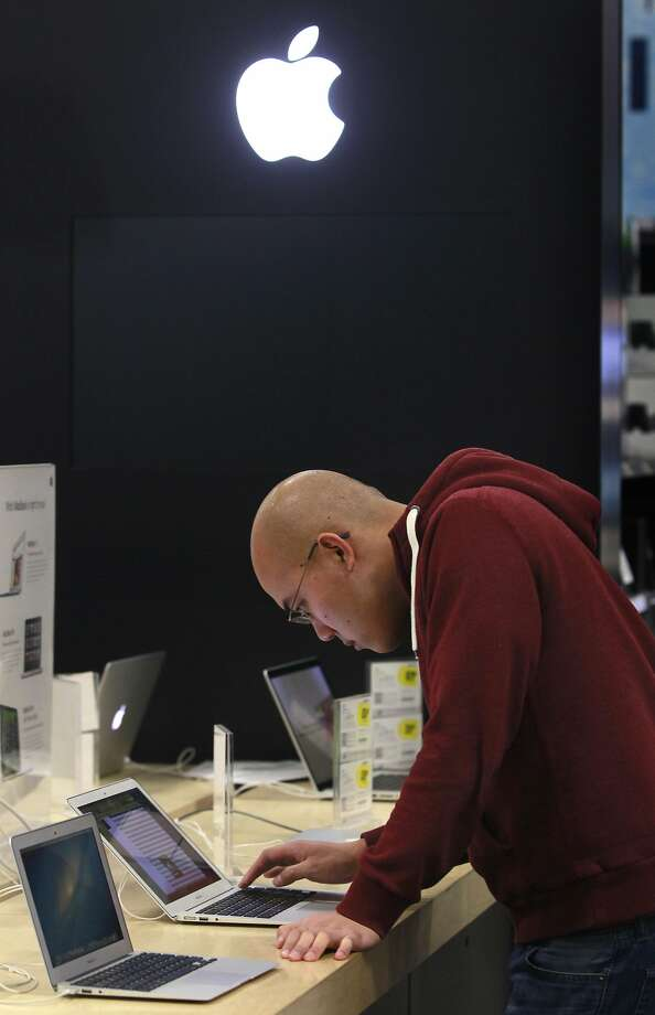 Alex Leong shops for a laptop computer during a lull in the Black Friday shopping rush at Best Buy in Oakland. New regulations would require Apple and other computer makers to increase devices' energy efficency. Photo: Paul Chinn, The Chronicle