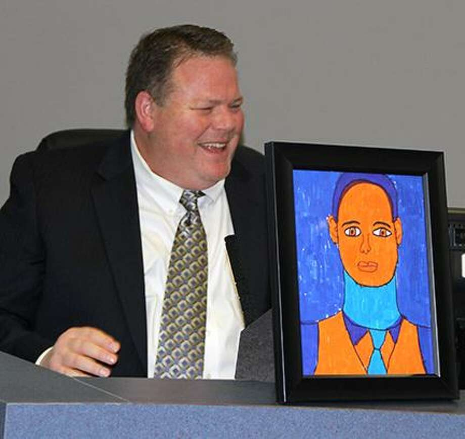 Brent Engelage beams during a past board meeting when a caricature of him drawn by a student. Photo: Courtesty Of Humble ISD
