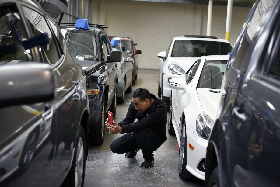 Cosmetic inspector Jovannie Tirona takes pictures of damage on a car at Shift's warehouse in South San Francisco. Photo: Michael Short, Special To The Chronicle