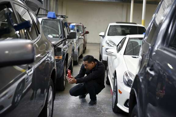 Cosmetic Inspector Jovannie Tirona takes pictures of damage spots on a car that need to be fixed before it is listed for sale, at Shift's headquarters in South San Francisco CA, on Wednesday, December 14, 2016.
