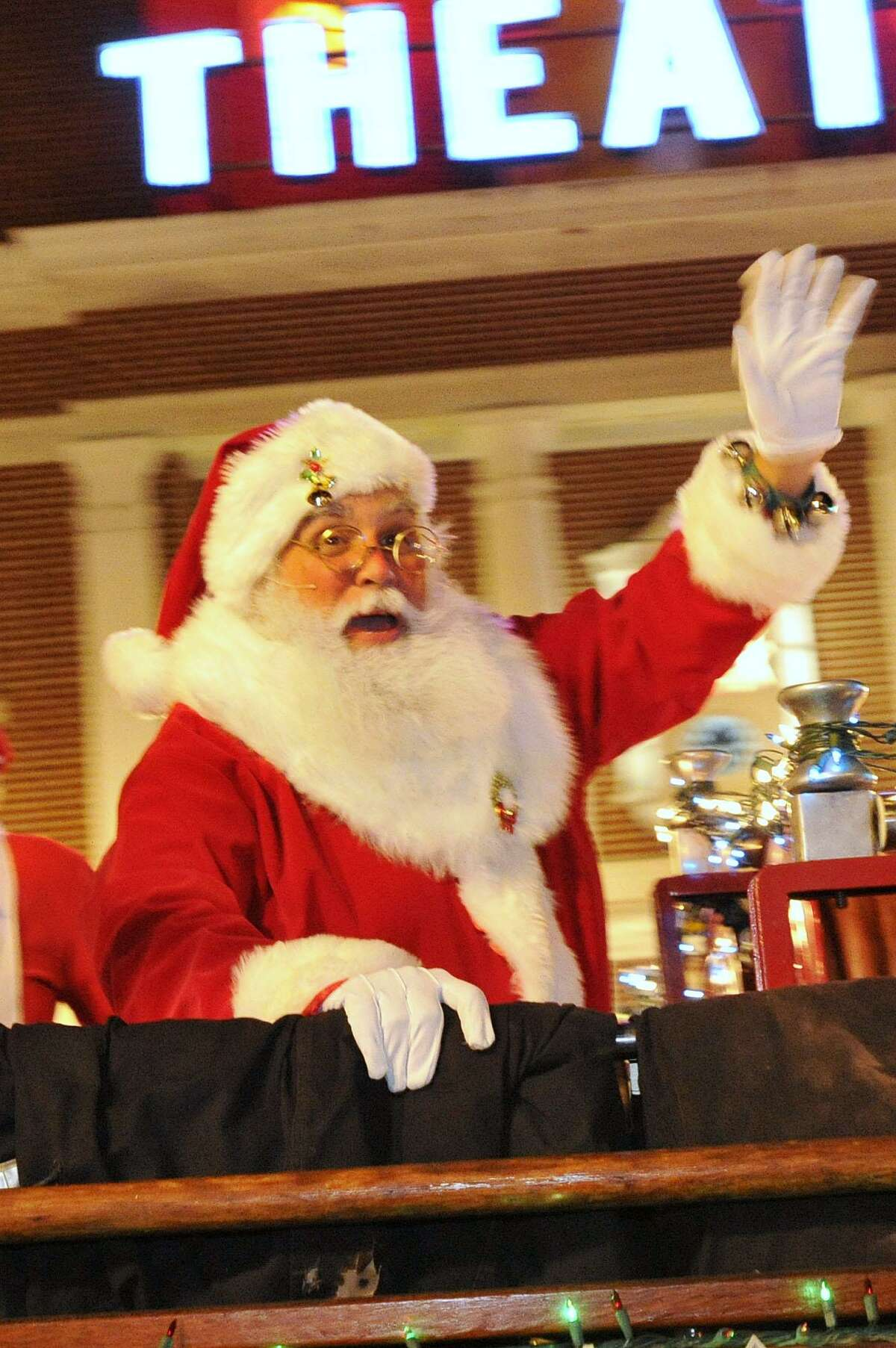 Santa waves to people on the street as he is escorted up Bedford Street during the Heights and Lignts Rappel and Tree Lighting event in downtown Stamford, Conn., on Sunday, Dec. 7, 2014.