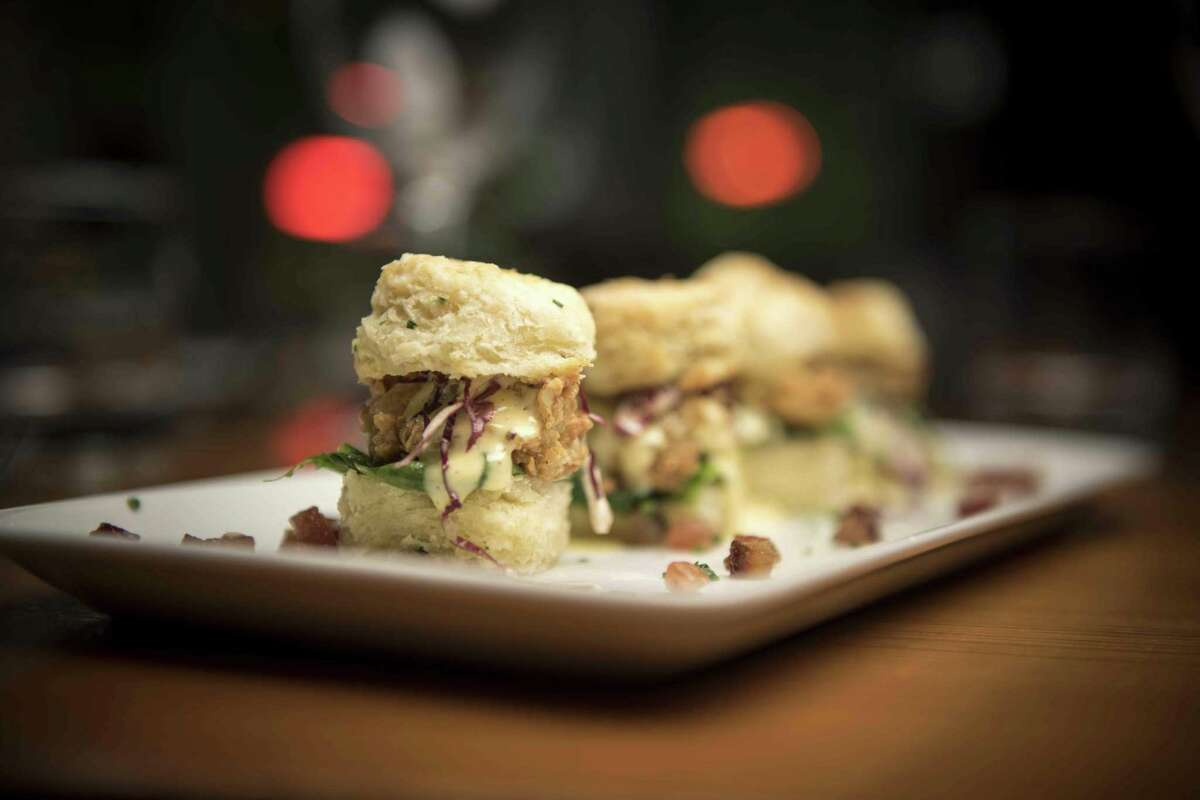 Oyster sliders with crispy fried Gulf oysters, candied bacon, buttermilk chive biscuits, spinach, brown butter hollandaise and chives from Bliss
