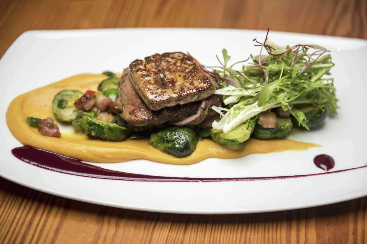 The duck and foie gras entree consists of grilled Szechuan peppercorn and five-spice crusted duck breast, seared foie gras, tri-colored peppers, Brussels sprouts with bacon, sweet potato puree and huckleberry gastrique.