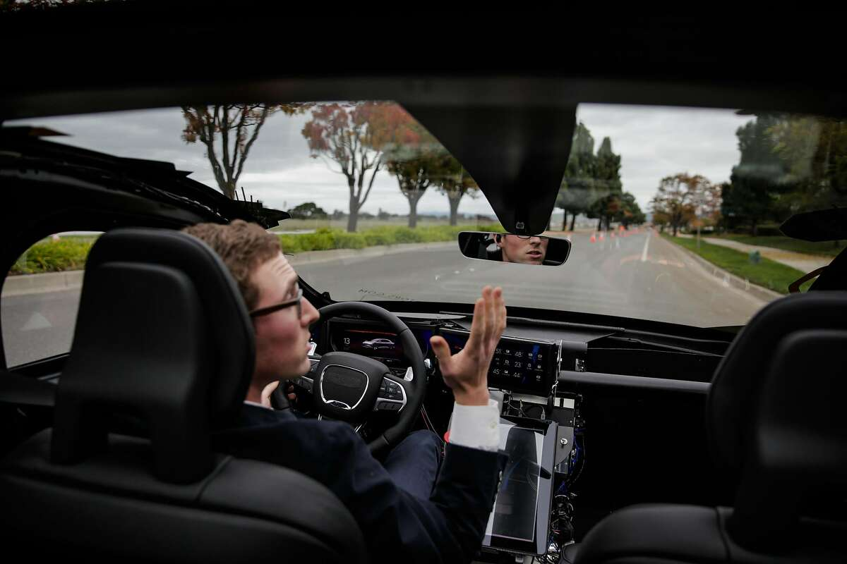 Software engineer Josh Goldberg takes his hands off the wheel while giving a test ride of a new Lucid luxury electric car at a media event, in Fremont, Calif., on Wednesday, Dec. 14, 2016.