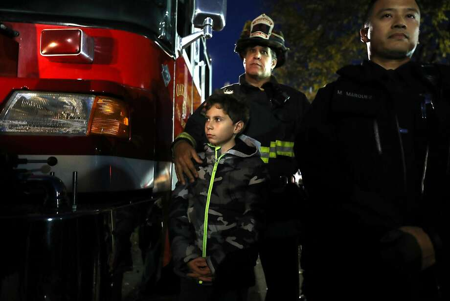 Oakland Firefighter Union President Lt. Dan Robertson and his son, Johnny., 10, during a memorial service for the Ghost Ship warehouse fire victims in front of the structure on 31st Avenue in Oakland, Calif., on Monday, December 12, 2016. Photo: Scott Strazzante, The Chronicle