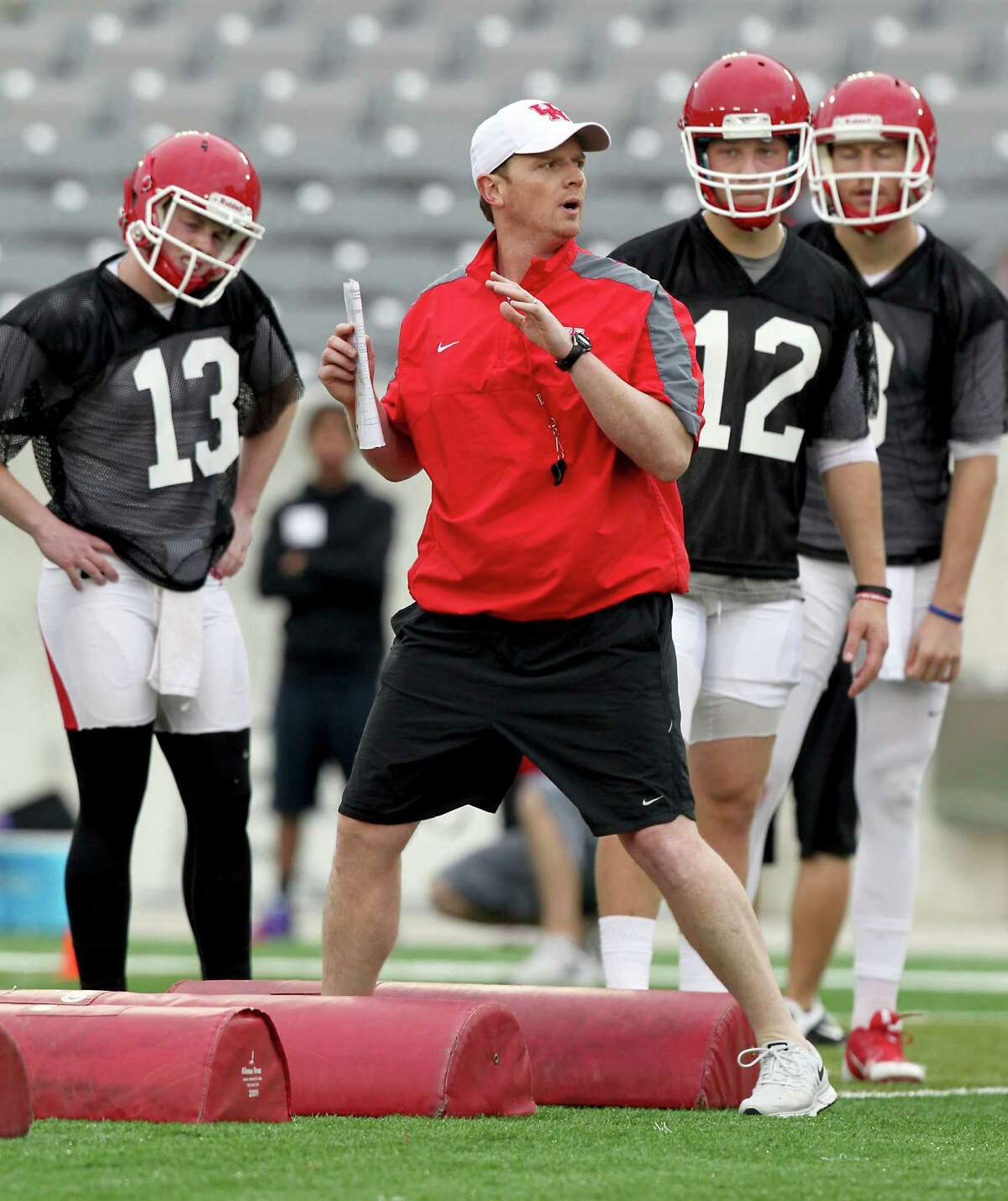 In this March 10, 2015 photo, Houston quarterbacks listen to quarterback coach Major Applewhite demonstrate a foot drill during spring NCAA college football practice in Houston. Applewhite was hired to replace Tom Herman as coach at Houston on Friday, Dec. 9, 2016. (Thomas B. Shea/Houston Chronicle via AP)