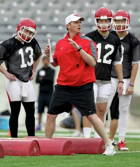 In this March 10, 2015 photo, Houston quarterbacks listen to quarterback coach Major Applewhite demonstrate a foot drill during spring NCAA college football practice in Houston. Applewhite was hired to replace Tom Herman as coach at Houston on Friday, Dec. 9, 2016. (Thomas B. Shea/Houston Chronicle via AP) Photo: Thomas B. Shea, MBO / ' 2015 Thomas B. Shea