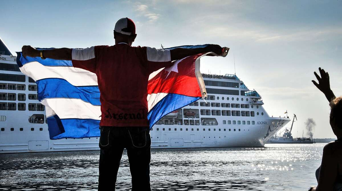 TOPSHOT - A man waves a Cuban flag at the Malecon waterfront as the first US-to-Cuba cruise ship to arrive in the island nation in decades glides into the port of Havana, on May 2, 2016. The first US cruise ship bound for Cuba in half a century, the Adonia -- a vessel from the Carnival cruise's Fathom line -- set sail from Florida on Sunday, marking a new milestone in the rapprochement between Washington and Havana. The ship -- with 700 passengers aboard -- departed from Miami, the heart of the Cuban diaspora in the United States. / AFP PHOTO / ADALBERTO ROQUEADALBERTO ROQUE/AFP/Getty Images