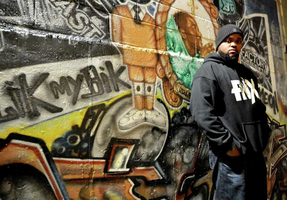 """Norwalk Rapper FNX stands near the mural depicting a tribute to one of the first Factory Underground artists, Stamford native Lighta, who passed away in 2011. FNX just released his debut album """"DJ Juelz Presents: FNX Music Vol. 1"""" and will be using it to raise awareness for feeding hungry families in the community through a crowd funding campaign, at The factory Underground in Norwalk Conn on Wednesday December 7, 2016 Photo: Alex Von Kleydorff / Hearst Connecticut Media / Connecticut Post"""