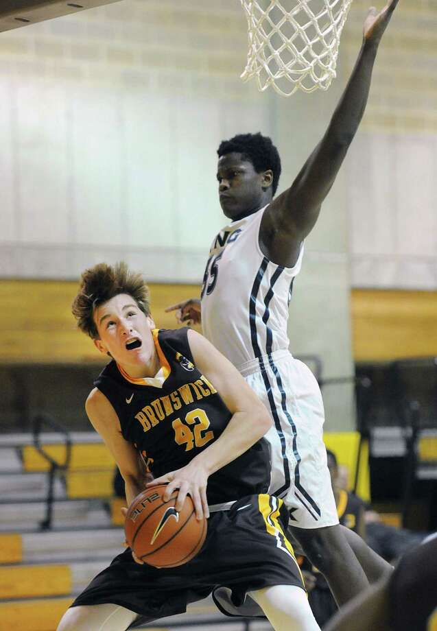 At left, Jack Molloy (42) of Brunswick attempts to score near the basket as Levaughn Lewis (35) of King goes high to defend during the boys high school basketball game between Brunswick School and King School at Brunswick in Greenwich, Conn., Wednesday, Dec. 14, 2016. King beat Brunswick 57-46. Photo: Bob Luckey Jr. / Hearst Connecticut Media / Greenwich Time