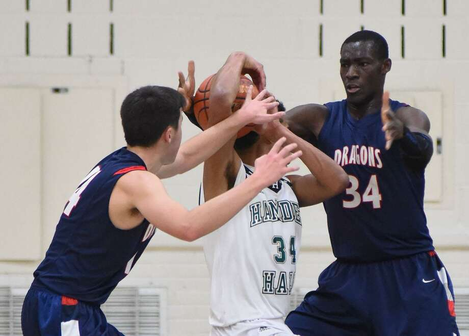 Greens Farms Academy defenders Sunday Okeke, right, and Greg Lawrence trap a Hamden Hall player during Wednesday's game at Coyle Gymnasium in Westport. Photo: Contributed Photo /
