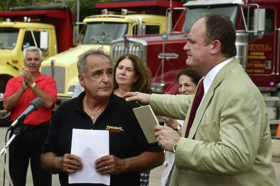 Vinny Penna, co-owner of A.J. Penna & Son Excavating Contractors at 10 Goldstein Place in Norwalk, Conn., is comforted by East Norwalk Business Association president, Winthrop Baum, during a rally at the Penna construction yard Wednesday, September 7, 2016, in an effort to save his business from the Connecticut Department of Transportation that has plans to take his property to help facilitate the Metro-North railroad Walk Bridge replacement project. Photo: Erik Trautmann / Hearst Connecticut Media / Norwalk Hour