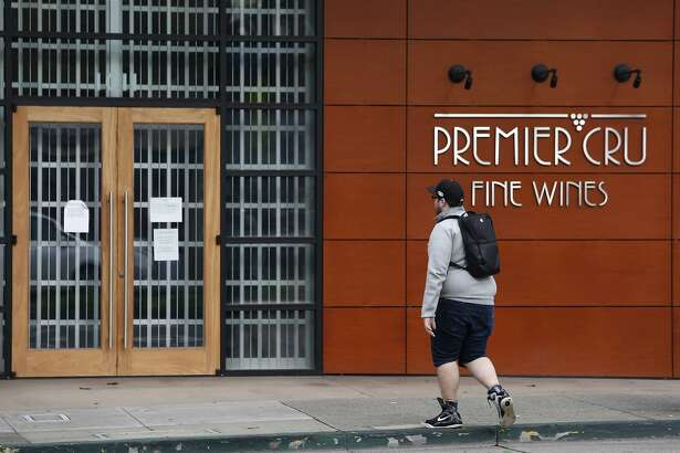 A man walks past the shuttered Premier Cru wine store on University Avenue in Berkeley, Calif. on Thursday, Jan. 14, 2016. Owners of the wine futures business filed for bankruptcy leaving customers in the lurch.