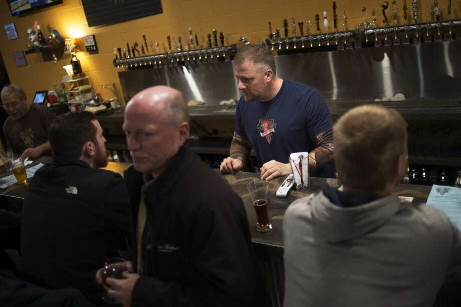 Bartender Ross Ruman takes an order at Tri-City Brewing Co.'s new location on Shrestha Dr. near Wilder Road and Euclid Avenue during their grand opening on Wednesday in Bay City. Tri-City Brewing Co. opened in 2007, and its new location is 10,000 square-feet. Photo: Erin Kirkland/Midland Daily News
