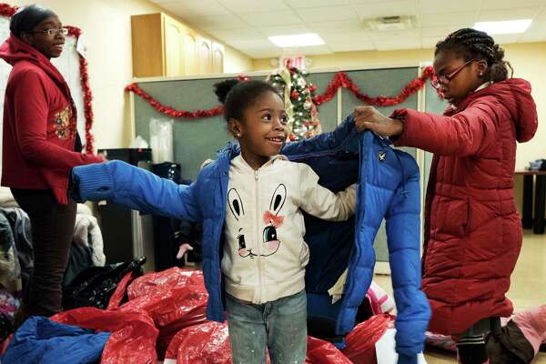 In this Dec. 9, 2016 photo, Gennine Moody, left, watches as her daughters Breonna, center, and Mychayla try on winter coats at the Neighborhood Association for Intercultural Affairs in the Bronx borough of New York. The used coats were donated as part of a collection and distribution effort by the New York Mets and New York Cares. (AP Photo/Mark Lennihan) ORG XMIT: NYR201