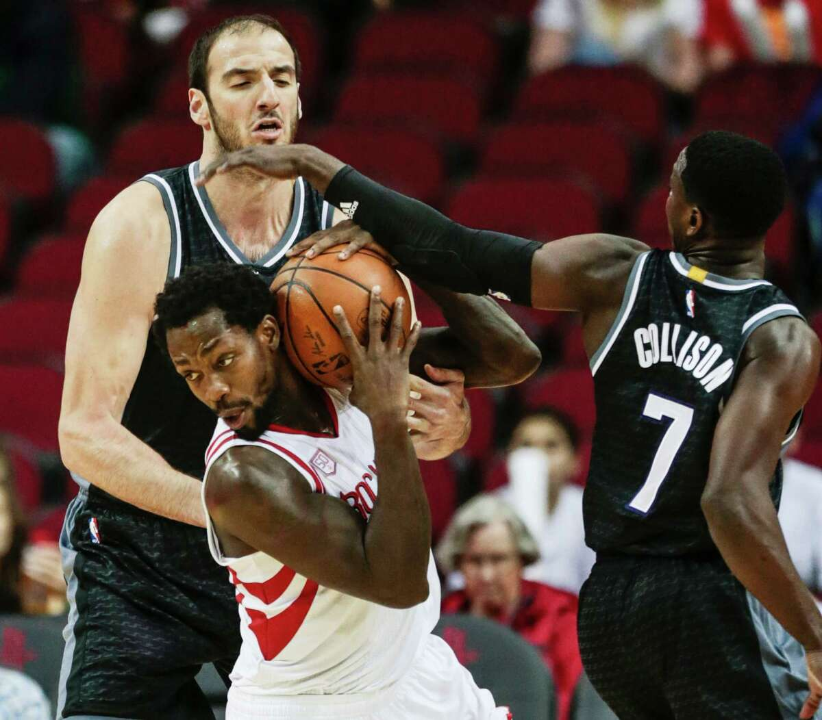 Rockets guard Pat Beverley pulls the ball away from the Kings' Kosta Koufos, left, and Darren Collison on Wednesday night at Toyota Center.