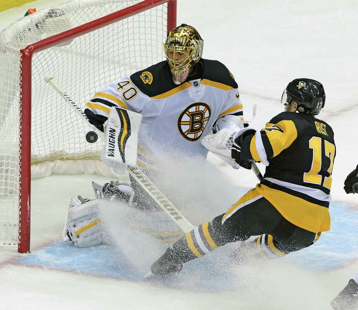Pittsburgh Penguins right wing Bryan Rust (17) shoots the puck past Boston Bruins goalie Tuukka Rask (40) during the overtime period of an NHL hockey game on Wednesday, Dec. 14, 2016, in Pittsburgh. The Penguins defeated the Bruins 4-3. (AP Photo/Fred Vuich) ORG XMIT: PAFV108