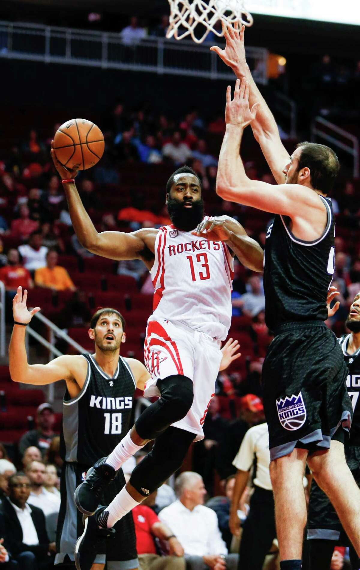 Rockets guard James Harden, center, finds a passing lane around Kings center Kosta Koufos on Wednesday at Toyota Center. Harden has become a triple-double machine this season with five.