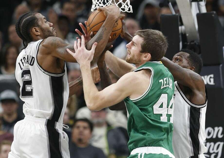Spurs' Kawhi Leonard (02) and Dewayne Dedmon (03) battle for a rebound with Boston Celtics' Tyler Zeller (44) during their game at the AT&T Center on Wednesday, Dec. 14, 2016. Spurs defeated the Celtics, 108-101.(Kin Man Hui/San Antonio Express-News) Photo: Kin Man Hui/San Antonio Express-News