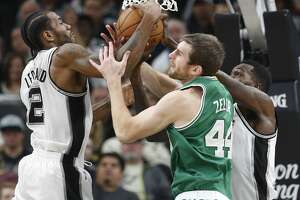 Spurs' Kawhi Leonard (02) and Dewayne Dedmon (03) battle for a rebound with Boston Celtics' Tyler Zeller (44) during their game at the AT&T Center on Wednesday, Dec. 14, 2016. Spurs defeated the Celtics, 108-101.(Kin Man Hui/San Antonio Express-News)