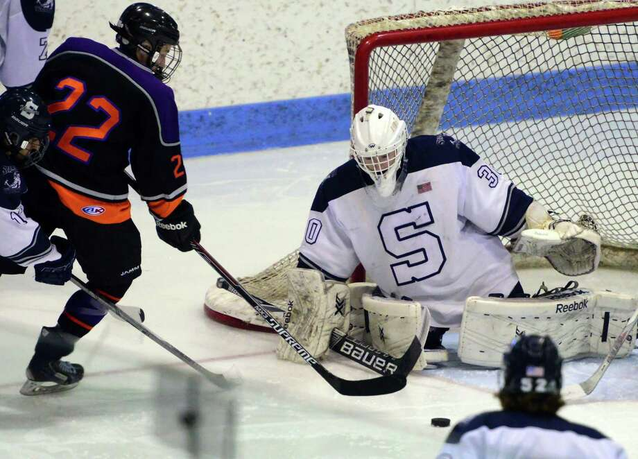 Staples-Weston-Shelton goalie Zachary Bloom deflects the puck as Westhill-Stamford's Owen Kilian tries to score during Division III boys hockey finals action in New Haven, Conn., on Saturday March 19, 2016. Photo: Christian Abraham / Hearst Connecticut Media / Connecticut Post