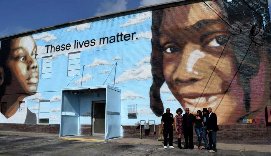 """Supporters of the Houston Museum of African-American Culture stand with artist Reginald Adams, second from right, in front of Adams' new mura, """"These Lives Matter,"""" at 5730 Calhoun, the first of several public art projects planned by the institution. Photo: Houston Museum Of African-American Culture"""