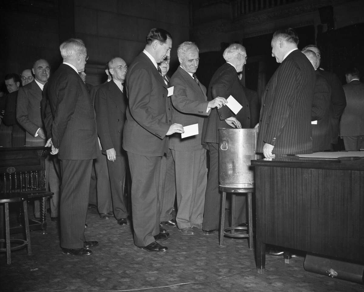 FILE - In this Dec. 16, 1940 file photo, New York State electoral college members cast votes at the state capital in Albany, N.Y. Most people who voted early or are heading to the polls on Nov. 8, 2016 think they will be voting for Democrat Hillary Clinton, Republican Donald Trump or their chosen third-party candidate. But they won't be. They'll be voting for their state's electors, who will in turn cast votes for the presidential candidate who wins the most votes in their state. (AP Photo)