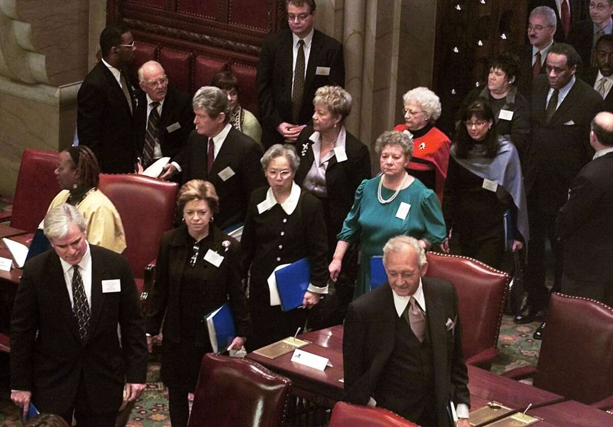 Members of the New York State 2000 Electoral College proceed into the State Senate Chamber, before casting their votes for United States president and vice president, Monday, Dec. 18, 2000, at the state Capitol in Albany, N.Y. (AP Photo/Suzanne Plunkett)