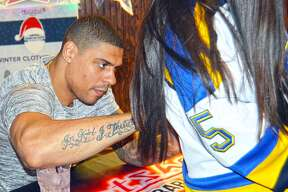 St. Louis Blues forward Ryan Reaves, left, signs the back of a fan's jersey during a Wednesday autograph session at Hotshots Sports Bar and Grill in Edwardsville. Fans started gathering at 3:30 p.m. to get a chance to meet Reaves, who arrived at 6:30 p.m. and signed memorabilia for 90 minutes.