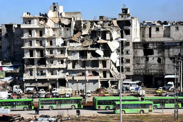 A general view shows buses waiting in front of destroyed buildings during an evacuation operation of rebel fighters and their families from rebel-held neighborhoods in the embattled city of Aleppo on December 15, 2016.